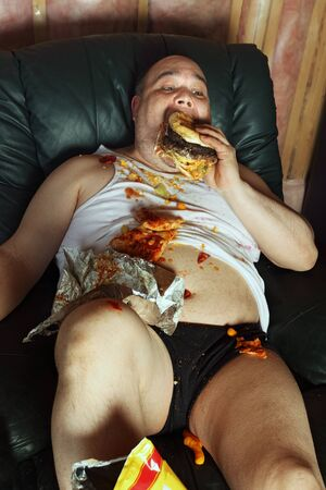 pregui�oso: Photo of a fat couch potato eating a huge hamburger and watching television.  Harsh lighting from the television illuminates the dark room. Banco de Imagens