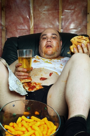 Photo of a fat couch potato eating a huge hamburger and watching television.  Harsh lighting from the television illuminates the dark room. photo