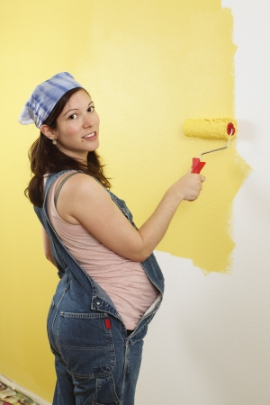 yellow walls: Photo of a pregnant female painting the wall of a bedroom for her future baby. Stock Photo