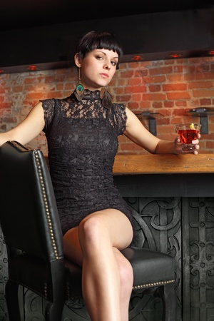 vertical bars: beautiful female at a bar, sitting on a leather chair holding a martini.