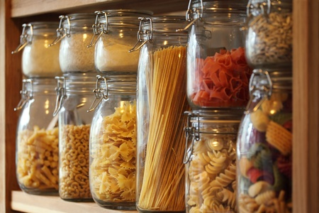 storage: Photo of dried pasta in jars on a shelf in a domestic kitchen.  Very shallow depth of field focusing on the middle jar. Stock Photo