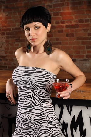 Photo of a beautiful female at a bar, standing holding a martini. photo