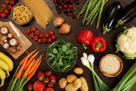 Photo of a table top full of fresh vegetables, fruit, and other healthy foods. photo