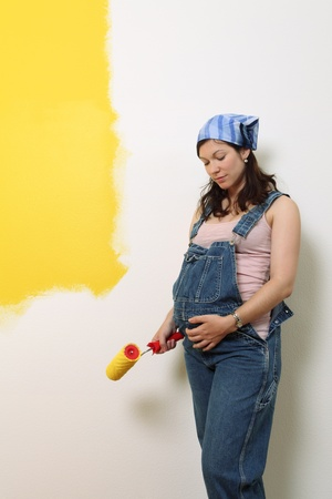 bedroom wall: Photo of a pregnant female painting the wall of a bedroom for her future baby. Stock Photo
