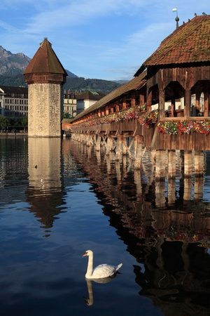 The Chapel Bridge and Lake Lucerne, in the city of Lucerne, Switzerland.  Photo taken early in the morning as the sun starts to rise. photo