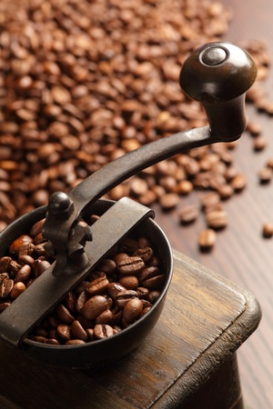 Photo of an antique coffee grinder with coffee beans in the blurred background. photo