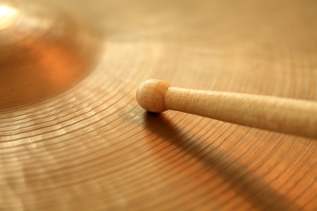 musical instruments: Photo of a drumstick playing on a hi-hat or ride cymbal.  Focus on tip of stick. Stock Photo