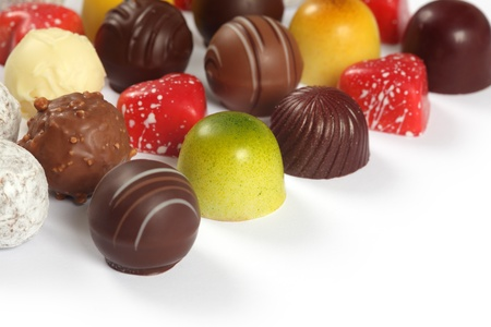 assorted truffles, pralines, and liqueur filled chocolates on white background.