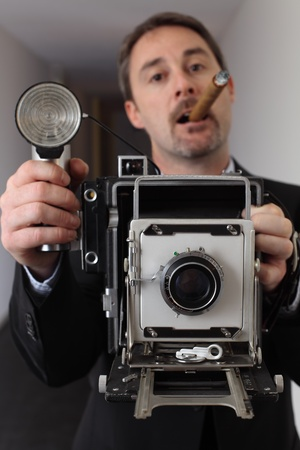 Photo of a retro 1940's style photographer taking a photo with an old 4x6 camera.  Photographer out of focus and camera in focus. Stock Photo - 10259570