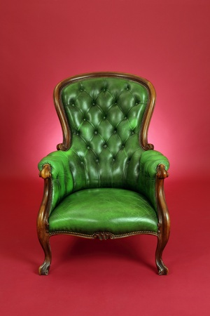 red chair: old antique green leather chair sitting on a red background.