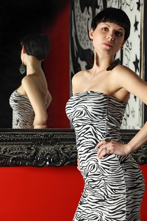 Photo of a sexy short-haired young female standing with her back to a mirror showing her reflection. photo