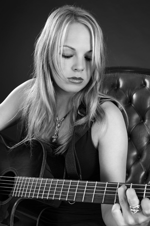 Photo of a beautiful blond female playing an acoustic guitar. photo