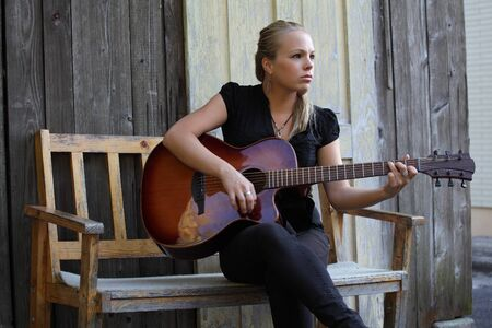 Photo of a beautiful blond female playing her acoustic guitar on an old wooden bench.   photo
