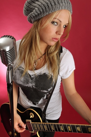 Photo of a gorgeous blond playing an electric guitar and about to sing into a retro microphone. Zdjęcie Seryjne - 10504283