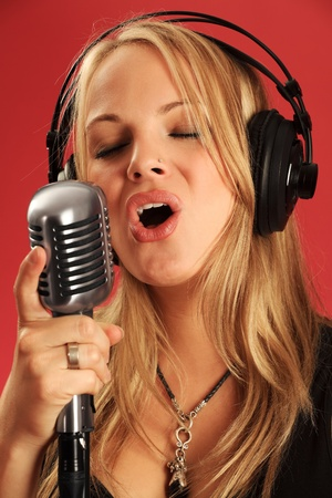 Photo of a beautiful young blond wearing headphones and singing into a vintage microphone. photo