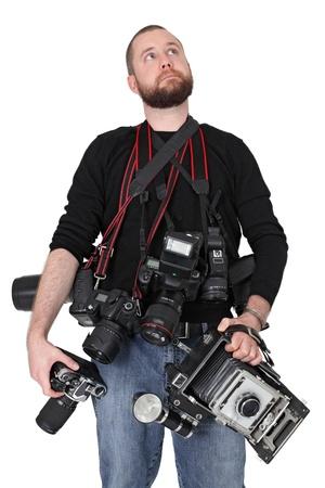 Foto van een man in zijn eind twintig, staande te houden veel camera's, film, digitale, medium formaat en groot formaat.