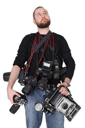 Photo of a man in his late twenties, standing and holding many cameras, film, digital, medium format and large format. photo