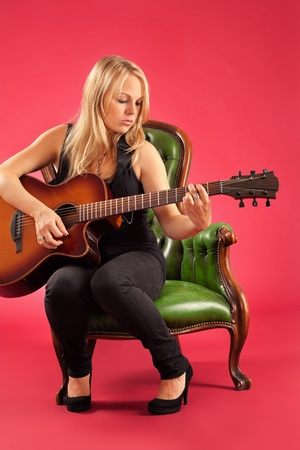 Photo of a female guitarist playing while sitting on a green leather chair. Stock Photo - 11312924