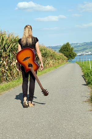 country lifestyle: Photo of a female guitarist walking down a country road with her guitar slung over her back.