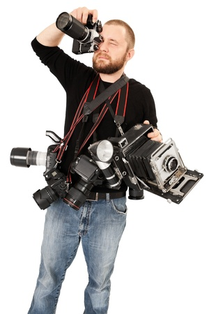 analogs: Photo of a man in his late twenties, standing and holding many cameras, film, digital, medium format and large format.