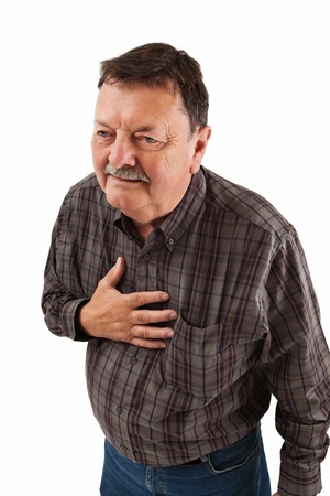 Photo of a man in his sixties having a dose of heartburn or pains in his chest. photo