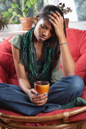 persona deprimida: Foto de una mujer triste, sentado en una silla sosteniendo una copa.