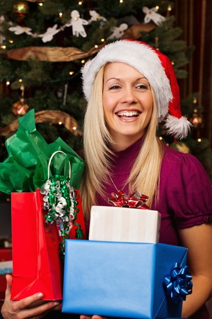 Portrait of beautiful young woman in Santa hat smiling while holding gift boxes. Stock Photo - 11312954