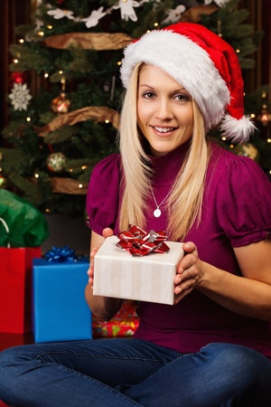 Portrait of beautiful young woman wearing Santa hat smiling while holding a present. Stock Photo - 11312967