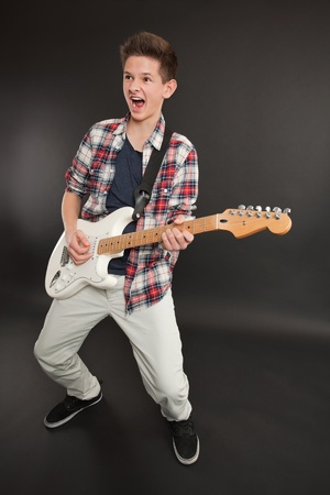 Photo of a teenage male playing a white electric guitar and making a rock and roll face. photo