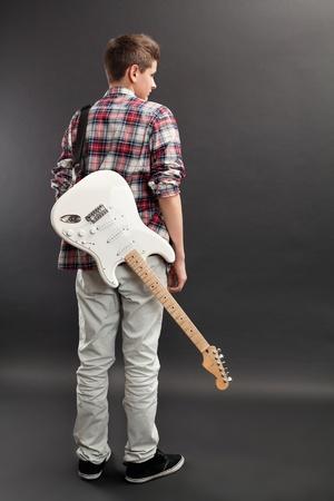 m�sico: Foto de un adolescente masculino de pie con una guitarra el�ctrica blanca colgando de su espalda. Foto de archivo