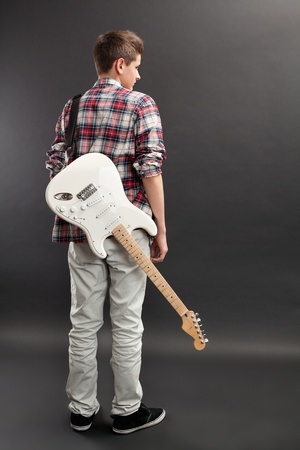 young musician: Photo of a teenage male standing with a white electric guitar slung over his back.