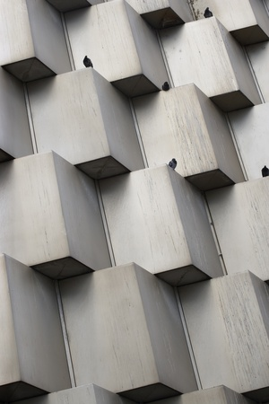 Abstract photo of a building facade with pigeons perched on top of the cubes. photo