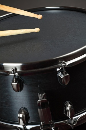 Drumsticks playing on a wood snare with black drum skin. photo