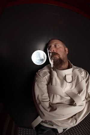 psychopathe: Photo d'un homme fou dans sa quarantaine porter une camisole de force appuy� contre une porte d'asile. Pris avec un objectif fisheye.