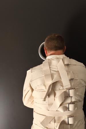insanity: Foto de un hombre loco de unos cuarenta a�os que llevaba un chaleco de fuerza buscando el agujero de una puerta de asilo. Foto de archivo