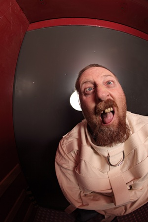 insane insanity: Photo of a insane man in his forties wearing a straitjacket leaning up against an asylum door.  Taken with a fisheye lens. Stock Photo