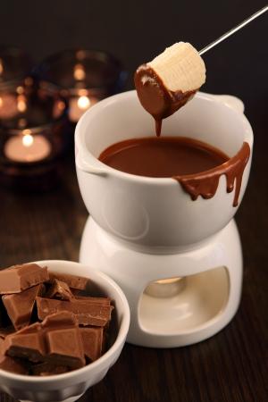 melt chocolate: Foto de una banana ser sumergido en el recipiente de la fondue de chocolate. Enfoque selectivo en la banana.