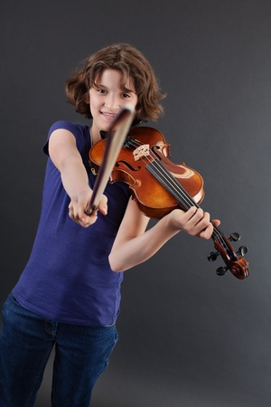 Photo of a young girl pointing the bow at the camera while playing the violin. photo