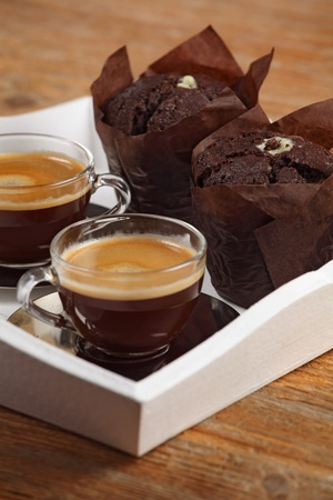Photo of two moist chocolate muffins and two cups of espresso or coffee resting on a white serving tray. Shallow depth of field focusing across middle of photo. photo