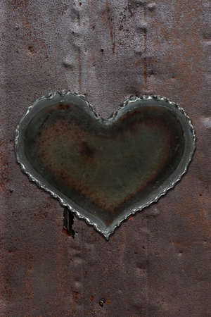 Photo of a metal heart attached to a sheet of rusty sheet metal. photo