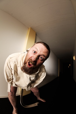 Photo of an insane man in his forties wearing a straitjacket standing in the hallway of an asylum.  Taken with a fisheye lens. photo