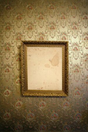 wall decor: Photo of an antique frame hanging on a wall with vintage wallpaper. Stock Photo