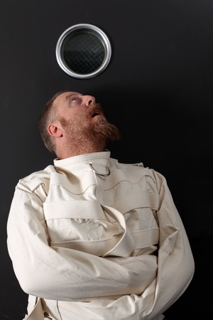 Photo of an insane man in his forties wearing a straitjacket crouched below the window of his cell. Stock Photo - 11873038