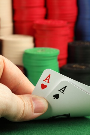 Photo of a card player holding two aces in focus, and a stack of gambling chips blurry in the background. photo