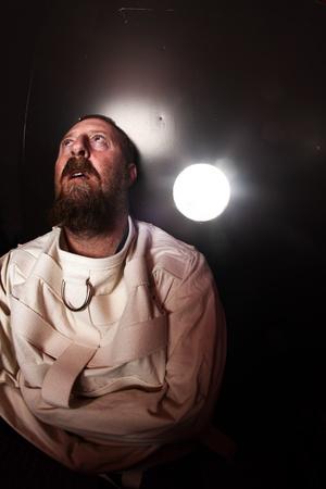 insanity: Foto de un hombre loco de unos cuarenta a�os que llevaba un chaleco de fuerza de pie en una celda de un manicomio con la luz del pasillo streaming in