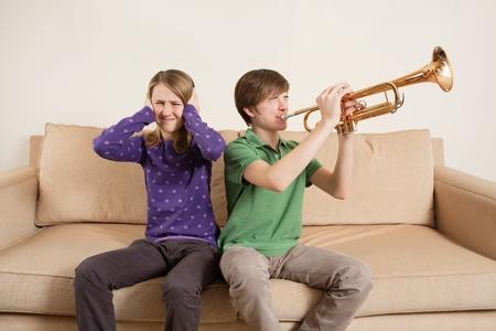 Foto de un hermano tocando su trompeta en voz demasiado alta, o mal, y su hermana molesta.