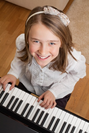 upright piano: Photo of a happy young girl playing the piano at home.