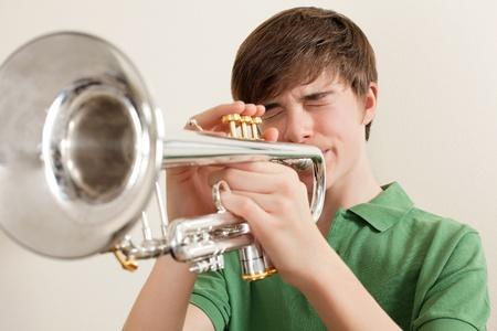 Foto van een jonge tiener speelt zijn zilveren trompet.