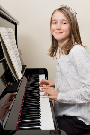 upright piano: Photo of a young girl playing the piano at home. Stock Photo