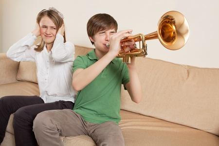 ruido: Foto de un hermano tocando su trompeta en voz demasiado alta, o mal, y su hermana molesta. Foto de archivo